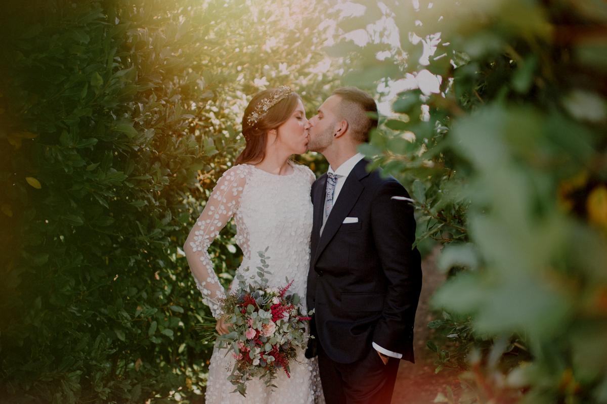 Pareja de recién casados en el Baserri Maitea se besan en el jardín del restaurante. Ella viste un vestido precioso de Alicia Rueda Atelier y el un traje de novio a medida de sastrería Bilbao.